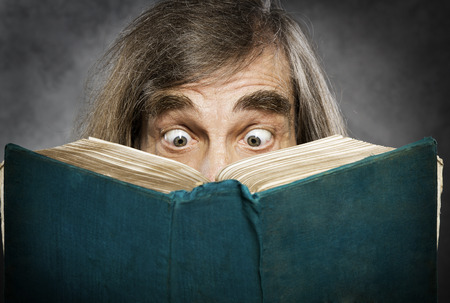 Senior reading open book, surprised old man, amazing eyes looking blank cover photo
