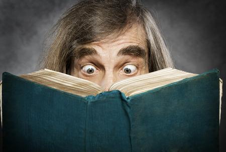 Superior libro abierto de lectura, viejo sorprendido, ojos increíbles que buscan portada en blanco