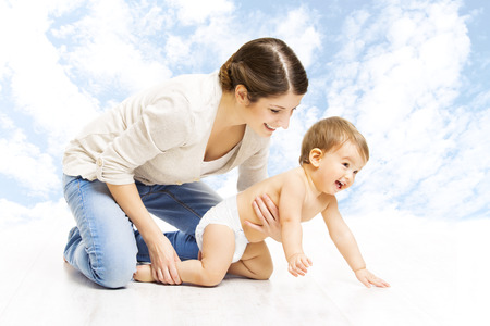 crawling baby: Mother baby happy playing. Child in diaper crawling over sky background  Stock Photo
