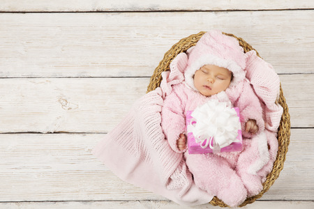Baby girl with gift sleeping on wooden background, newborn in basket with present. Birthday party invitation card photo