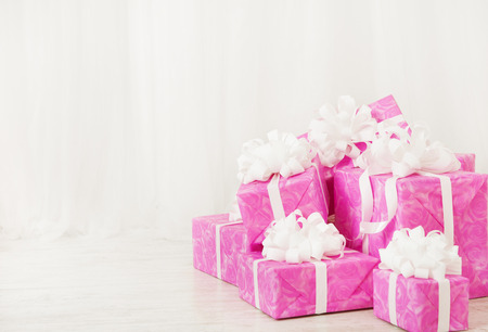 presents gift boxes stack, birthday in pink color for female or woman, over white background photo