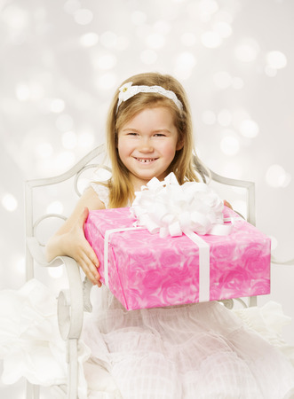 Girl holding birthday present. Happy little child with party gift box in pink color. photo