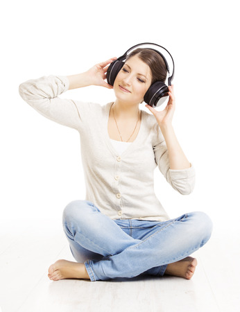Woman in headphones listening to music. Woman portrait isolated over white background photo