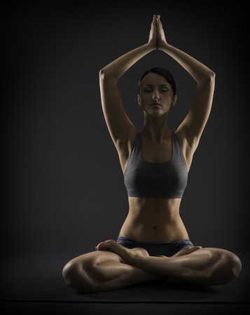 woman black background: Yoga woman meditate sitting in lotus pose. Silhouette of exercise girl over black background.