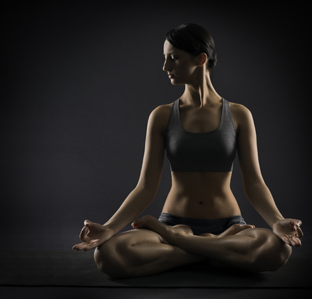 Yoga woman meditate sitting in lotus pose. Silhouette of exercise girl over black background.  photo