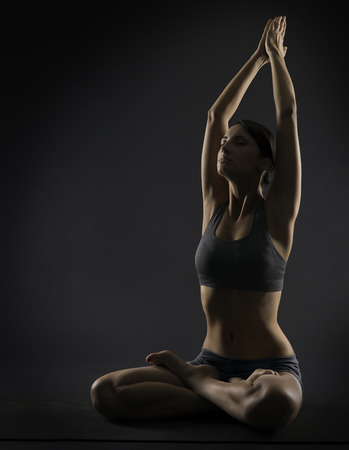 Yoga woman meditate sitting in lotus pose. Silhouette of exercise girl over black background.