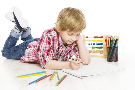 niños estudiando: Niño de la escuela escrito en ejercicio colegial cuaderno hacer una suma de tareas de matemáticas, aislado en fondo blanco Foto de archivo
