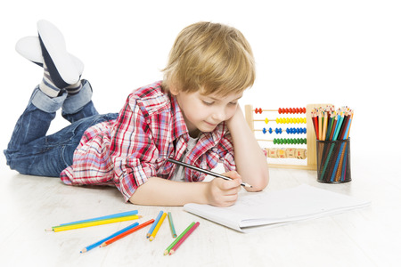 child studying: School boy writing exercise in notebook  Schoolboy do a sum of mathematics homework, isolated on white background  Stock Photo
