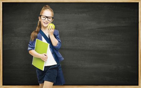 school desk: Schoolgirl with book apple and blackboard, school girl child on black board background, elementary education concept Stock Photo