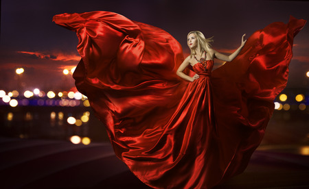 woman dancing in silk dress, artistic red blowing gown waving and flittering fabric, night city street lights Banque d'images