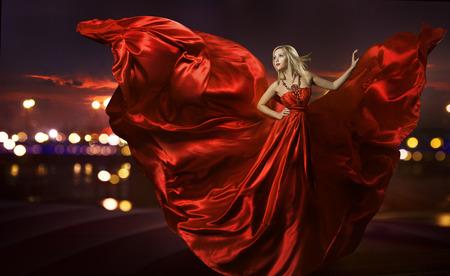vestido de noche: mujer bailando en vestido de seda, vestido artístico soplado rojo saludando y flittering tela, luces de la calle la noche de la ciudad