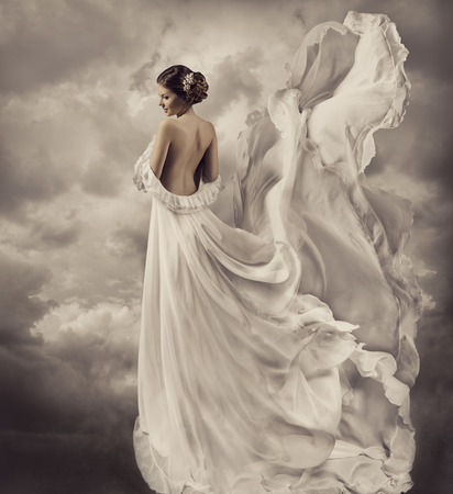 woman portrait in retro dress, artistic white blowing gown, waving and fluttering fabric, fantasy wedding bride