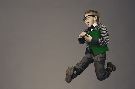 child running back to school, funny kid portrait, jumping smart schoolboy with glasses and book Stockfoto