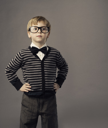hand on hip: boy in glasses, little child portrait, kid smart casual clothing, arms on hips Stock Photo