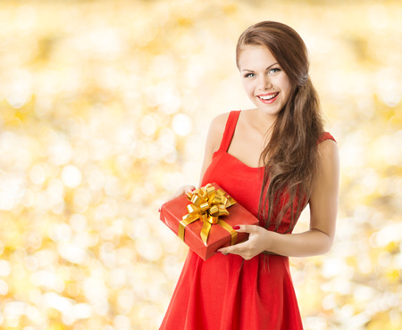 autumn present gift box, smiling woman holding presents over fall leaves yellow background photo