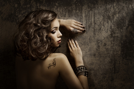 Woman Tattoo on back shoulder, sexy girl beauty fashion portrait over grunge background