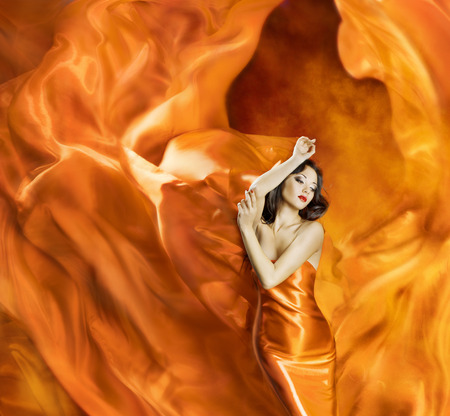 Woman dancing silk dress fire flame artistic orange burning blowing gown   Stock Photo