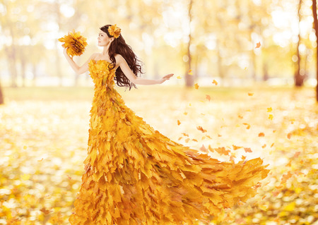 Autumn woman in fashion dress of fall maple leaves, artistic portrait in yellow gown