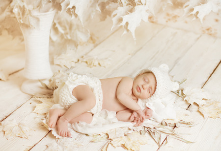 a young baby: Newborn Sleeping Baby Portrait, New Born Little Child Lying On Autumn White Art Leaves, Dreaming Bedtime Story Stock Photo