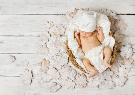 Newborn baby sleeping in basket on leaves over white wooden background. Stock Photo