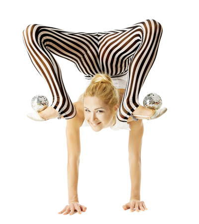 upside down: circus gymnast woman flexible body standing on arms upside down, balancing balls on feet. Isolated white background Stock Photo