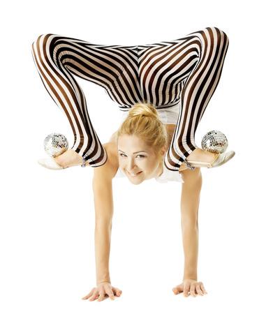 cuerpo flexible circo Gimnasta de la mujer de pie en los brazos al revés, el equilibrio de las bolas en los pies. Aislado fondo blanco