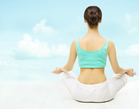 Yoga woman back view meditate sitting in lotus pose over sky background.  photo