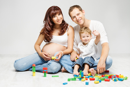 Happy family. Parents with  kid playing blocks over white photo