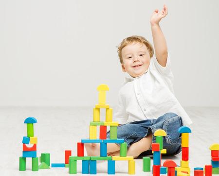 Child playing toy blocks over white photo
