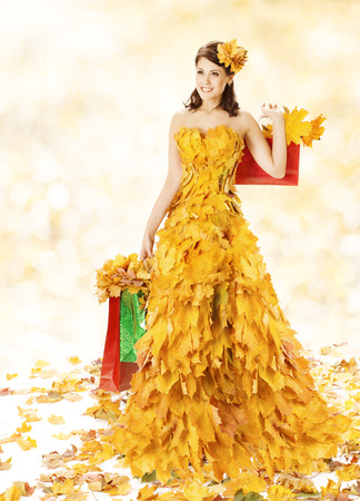 Shopping Woman Happy In Autumn Fashion Dress Of Yellow Fall Leaves With Paper Bags, Girl Spree Walking  After Autumnal Clearance Sale in Shopping Mall photo