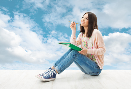 Girl teenager thinking inspiration or write idea, sitting over blue sky background