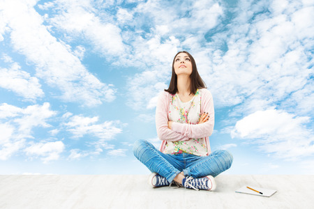 blue sky thinking: Girl teenager thinking inspiration or planning idea, sitting over blue sky background  Stock Photo