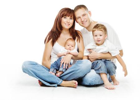 Молодые семьи четыре человека, улыбаясь отец мать и двое детей сыновей, на белом фоне Фото со стока