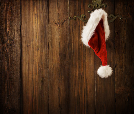 Christmas Santa Claus Hat Hanging On Wood Wall, Xmas Concept, Decoration Over Grunge Wooden Background Stock Photo