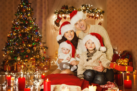 Christmas Family Portrait In Home Holiday Living Room, Kids and Baby at Santa Hat With Present Gift Box, House Decorating By Xmas Tree Candles Garland photo