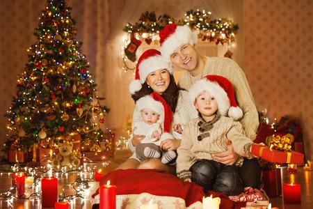 kerst interieur: Kerst familieportret in de woning Holiday Living Room, Kinderen en Baby in Santa Hoed Met Present Gift Box, House Decorating Door Xmas Tree Kaarsen Garland