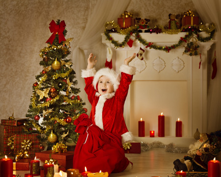 Christmas Kid Boy In Santa Hat And Bag, Child Happy Celebrate New Year, Room Decorated by Xmas Tree Present Gift Boxes and Candles