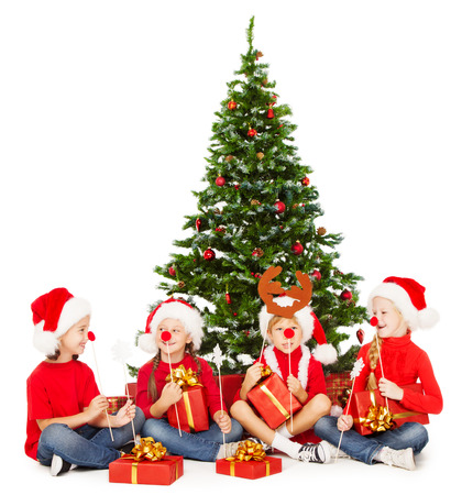 Christmas kids in Santa hat playing under fir tree. New year presents and accessories photo