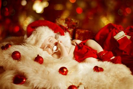 Christmas Baby, New Born Kid Sleeping As Xmas Gift In Santa Hat, Newborn Child Dreams In New Year Decoration photo