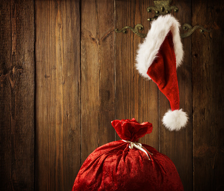 hanging sign: Christmas Santa Claus Hat Hanging On Wood Wall, Xmas Concept, Decoration Over Grunge Wooden Background Stock Photo