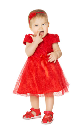 Baby Girl in Red Dress. Happy Kid in Fashion Holiday Clothes Suck Finger in Mouth. Child Isolated White Background photo