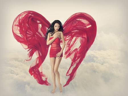 女性の天使の翼の織布のハート形としてファンタジー空雲を背景に飛んで、赤いドレスのファッション モデルの女の子