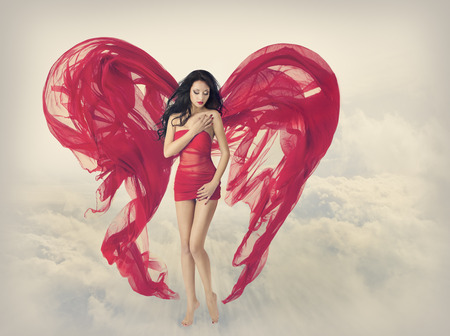 Woman Angel Wings as Heart Shape of Fabric Cloth, Fashion Model Girl in Red Dress, Flying on Fantasy Sky Clouds Background photo
