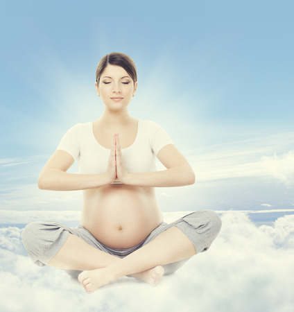 pregnancy yoga: Pregnant Woman Yoga Meditation. Pregnancy Health Wellness and Relax Exercising. Mother Sitting in Lotus Position Crossed Legs over Sky Background
