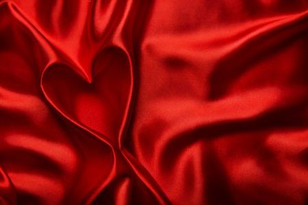 ハートの形、赤絹の布の背景、抽象的なバレンタインの日空背景として生地の折目