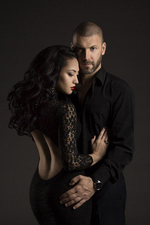 two girls hugging: Couple Man and Woman in Love, Fashion Beauty Portrait of Models Embracing over Black Background