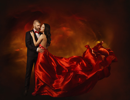 evening gown: Elegant Couple Dancing in Love, Woman in Red Clothes and Lover Man in Classic Suit, Long Waving Dress Tail, Fashion Beauty Portrait
