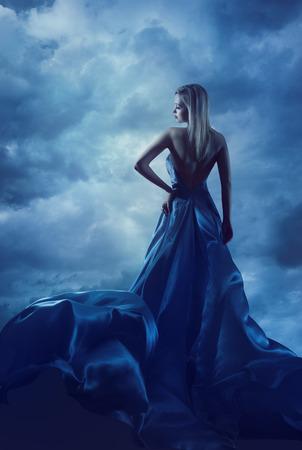 traje de gala: Espalda de la mujer del retrato en vestido de noche, Se�ora en vestido de seda, pa�o del vuelo sobre el cielo azul, nubes de la noche Foto de archivo