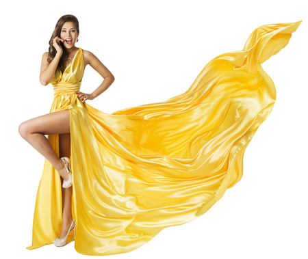 gown: Woman Beauty Fashion Dress, Beautiful Girl In Flying Yellow Fluttering Gown, Standing on One Leg High Heels, Surprised with Open Mouth. Fabric Cloth Waving on Wind, Isolated Over White Background