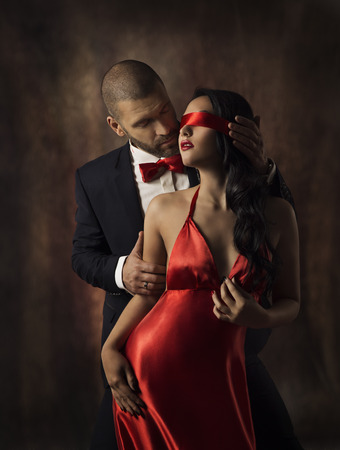 Couple in Love, Sexy Fashion Woman and Man, Girl with Red Band on Eyes Charming Boyfriend in Suit, Glamor Model Portrait, Valentine Day Lovers Sensual Games photo